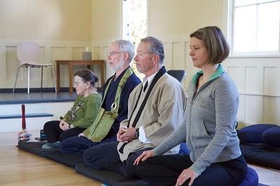 four people meditating