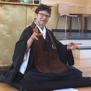 Buddhist teacher Genko Kathy Blackman sitting on a cushion, gesturing during a dharma talk.