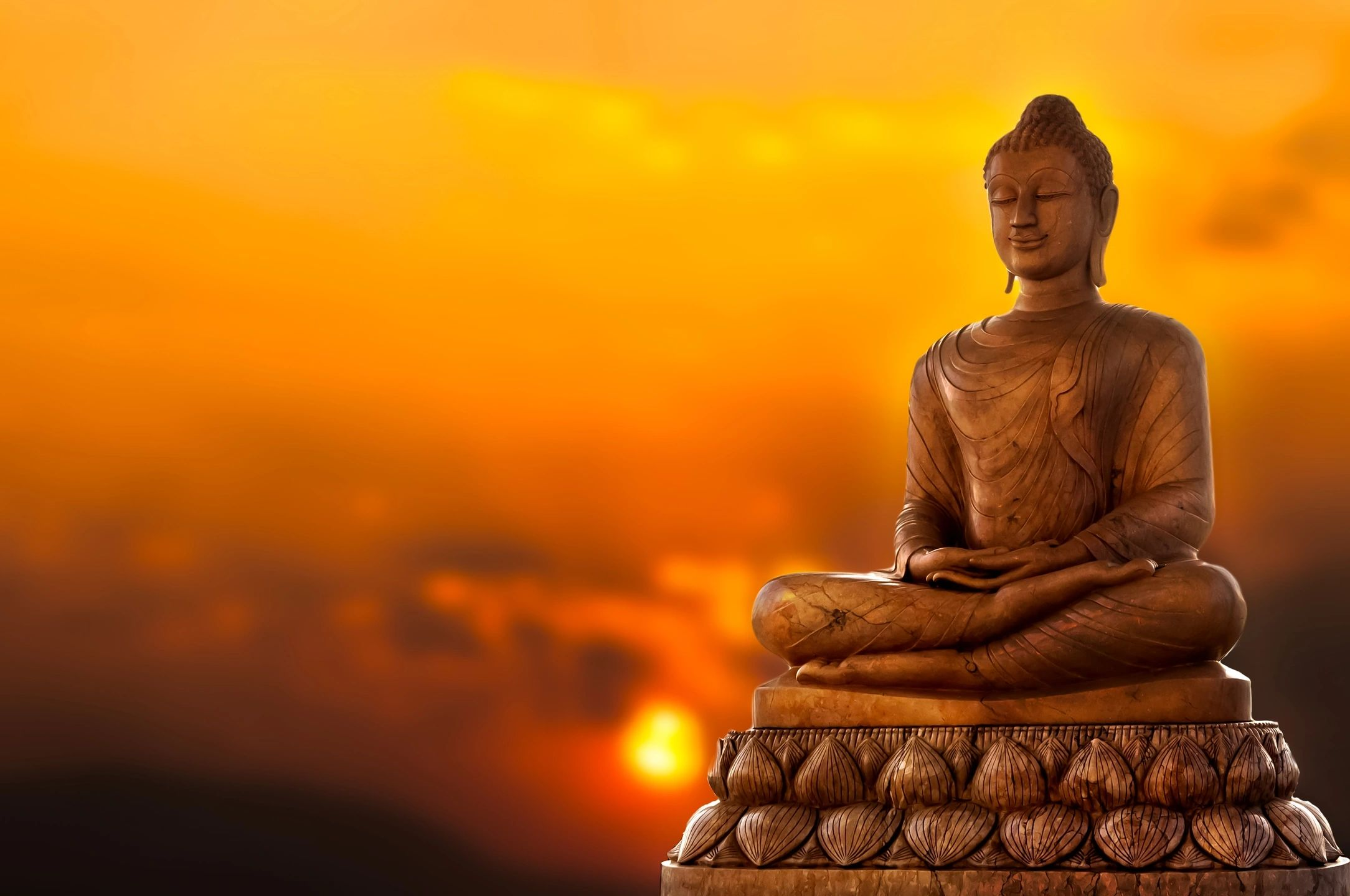 golden Buddha meditating on lotus leaves with a sunset behind him