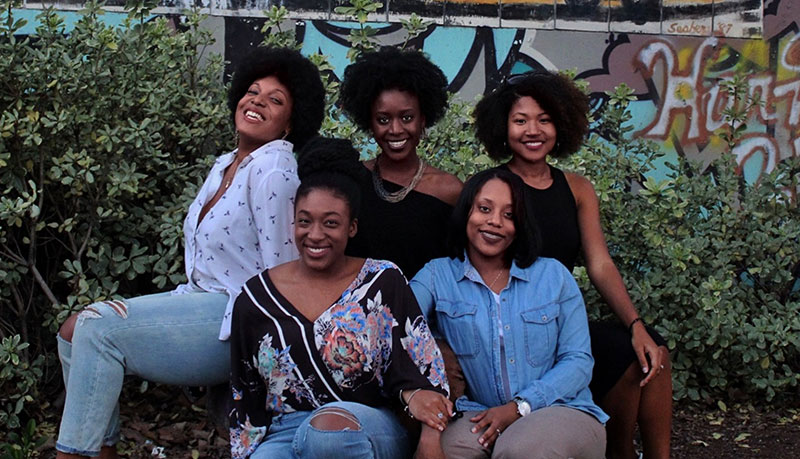 5 women of color sitting in front of bushes and a graffiti wall