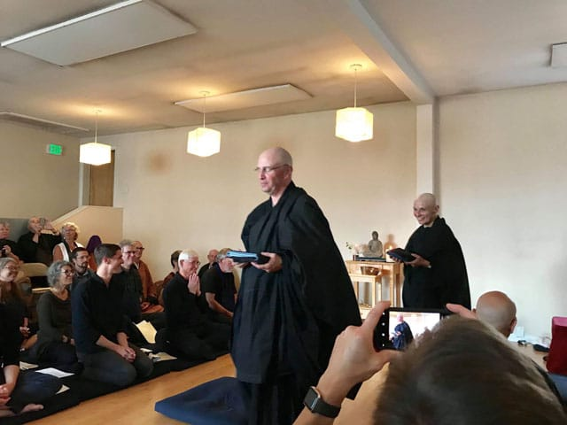 Two Zen priests in a ceremony with many Buddhists on cushions watching.
