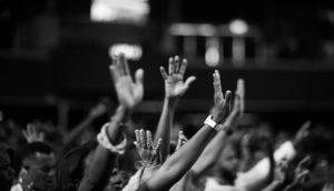 hands raised in protest at night, asking for racial justice..
