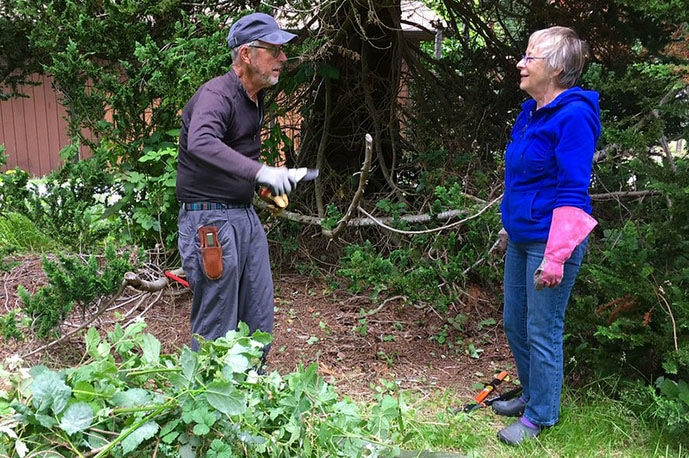 2 people working to tidy the Zen Center's grounds.