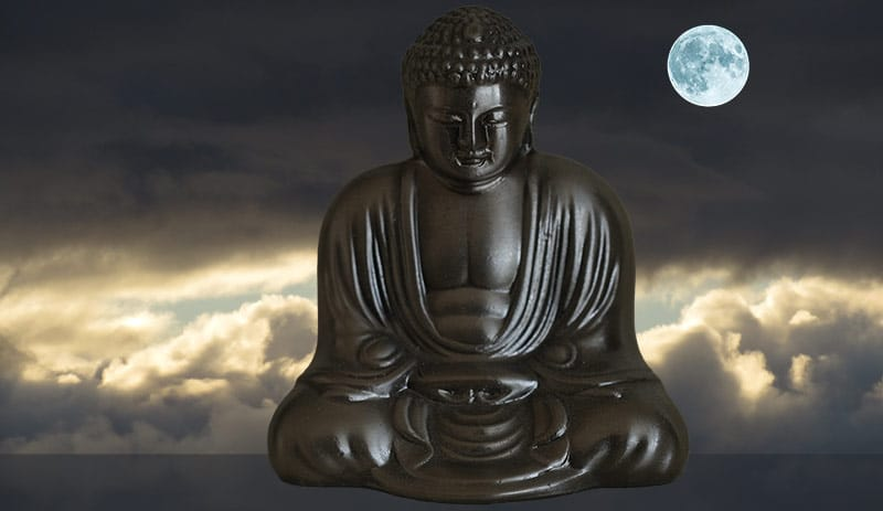 metal Buddha in meditation with a moon and sunrise behind him